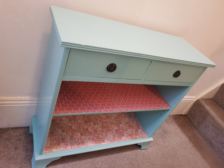 A sideboard painted blue, with pink patterned paper lining the shelves.